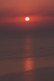 Red sunrise over the sea, vertical shot. Beautiful sunrise over the sea in deep red colors with round sun and clouds Royalty Free Stock Photo
