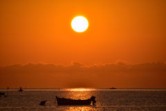 Red sunrise with silhouette of boat. Royalty Free Stock Image