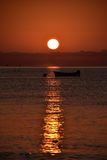 Red sunrise with silhouette of boat. Stock Photo