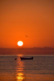 Red sunrise with silhouette of boat. Royalty Free Stock Images