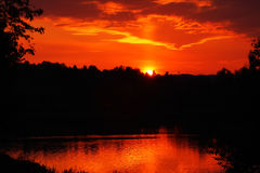 Red sunset. In the lake. Dark forest Stock Photo