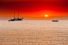Red sunset behind the mountains over sea and ships Stock Image