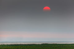 Red sunset in a haze. The smoke from wildfires in BC Interior has wafted into Vancouver. The smoke has made the sun turn red. Aug 2017 Royalty Free Stock Images