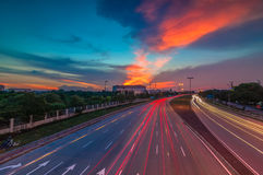 Red sunset and light trail. Light trail during sunset near traffic at industrial area stock images