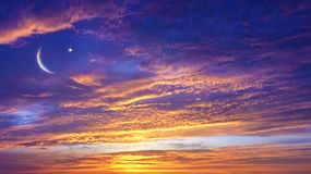 Sunrise . Light from sky . Religion background . Red sunset and moon . Eid Mubarak background . Against the background of clouds . beautiful sky . Nasa . Yellow royalty free stock image