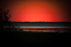 Red sunset near pond royalty free stock image