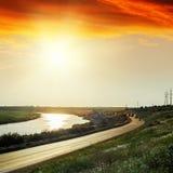 Red sunset over asphalt road near river Royalty Free Stock Image