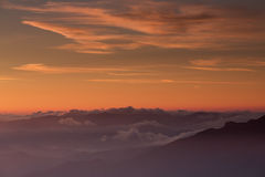 Red sunset over clouds and mountain Stock Image