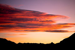 Red sunset over mountains silhouette. A landscape shot of a red and pink sunset over the mountains royalty free stock image