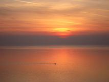 Red sunset over the ocean and little boat Royalty Free Stock Images