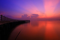 Red sunset over sea and pier. Scenic view of red sunset and cloudscape over calm sea with silhouetted pier Stock Images