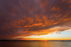 Red sunset over the sea, rich in dark clouds, rays of light Stock Image