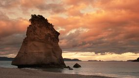 Red sunset at cathedral cove, nz. Red sunset at the popular cathedral cove on new zealand`s coromandel peninsula stock footage