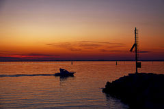 Red sunset on sea with solitary motor boat Stock Images