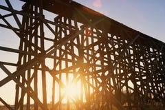Red sunset shining through scaffolding of elevated train bridge Royalty Free Stock Image