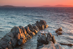 Red sunset. Stone dinosaur enters the water at sunset. Mykonos Royalty Free Stock Photo