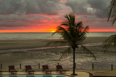 Red sunset on a tropical beach in a swimming pool resort Stock Photo