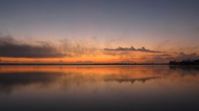 A red sunset. Waiting the moon to show strong by the lake of Bacalar in Quintana Roo, México Stock Photo