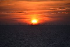 Red sunset with windfarm at sea Stock Photography