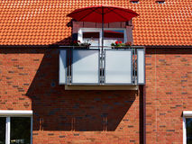Red sunshade parasol on a modern balcony Royalty Free Stock Images