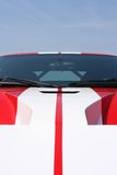 Red supercar. Front of red super car with white stripes and blue sky background Royalty Free Stock Photo
