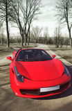 Red supercar. Against narrow abandoned road stock photo
