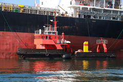 Red support tug and big cargo ship Stock Image