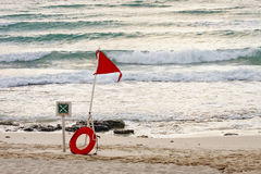 Red Surf Warning Flag and Life Ring on Beach Royalty Free Stock Images