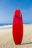 Red surfboard. Beach landscape with a red surfboard on the sand royalty free stock images