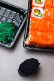 Red sushi set with salmon, orange caviar, cucumber, avokado, and black gunkan with green algae on grey background. Japan food Royalty Free Stock Photo