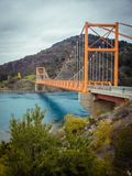 Red suspension bridge over the water runoff of General Carrera Lake, near Lake Bertrand, Puerto Tranquilo, Chile Chico, Aysen,. Chile royalty free stock image