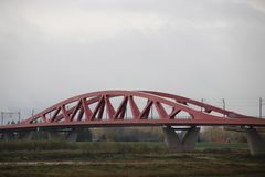 Red suspension bridge of steel over river IJssel at Zwolle in the Netherlands for trains. Red suspension bridge of steel over river IJssel at Zwolle in the stock photo