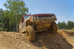 Red SUV overcomes steep muddy slope. Stock Photography