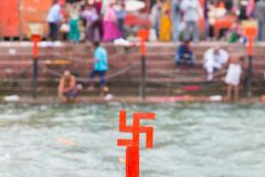 Red swastika cross on the Ganges River at Haridwar, India, sacred city for Hindu Religion. Pilgrims bathing on the ghats. Stock Photos