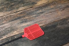 Red  swatter  fly, object  made of plastic on Wood floor background. With copy space add text Royalty Free Stock Photos