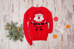 Red sweater with Santa on a wooden background. Fur-tree branch with Christmas decorations Royalty Free Stock Photography