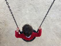 Red sweater tousled boy sitting in a swing royalty free stock images