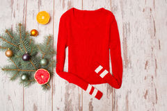Red sweater on a wooden background. Fur-tree branch with Christmas decorations Stock Photography