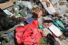 Red sweatshirt in the middle of rubbish heaps and many rags in a. Homeless camp after the forced eviction of the police Royalty Free Stock Photography