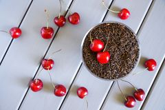 Red sweet cherry and black tea on a light wooden background. New fruity flavor favorite drink. Harvest time. View from above stock image