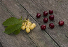 Red sweet cherry and branch of white sweet cherry on the old desktop Royalty Free Stock Photo