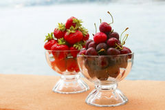 Red sweet cherry and strawberries in  glasses Stock Photography