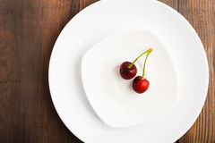 Red sweet cherry on two white plates Royalty Free Stock Images