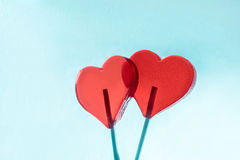 Red sweet hearts on pastel background. Lollipop Stock Photo