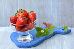 Red, sweet, homemade strawberry in transparent dish and blossoming flower on blue, wooden board. On white background Stock Image