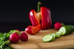 Red sweet pepper paprika, green sliced cucumber. Radishes with Royalty Free Stock Photography