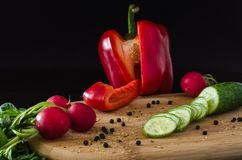 Red sweet pepper paprika, green sliced cucumber, radishes with a bunch of greens and spilled spice. Of black pepper on light wooden board, on black background Royalty Free Stock Image