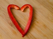 Red sweet pepper paprika in shape of heart with two pieces. On light wooden background Royalty Free Stock Image