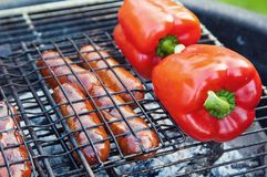 Red sweet pepper and sausages on a grill, close up Stock Photography