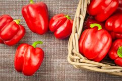 Red sweet pepper in wicker basket on textile background canvas, close-up, top view royalty free stock photos